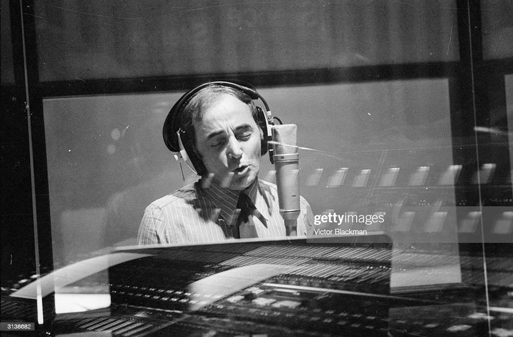 French singer and songwriter Charles Aznavour performing in a recording studio