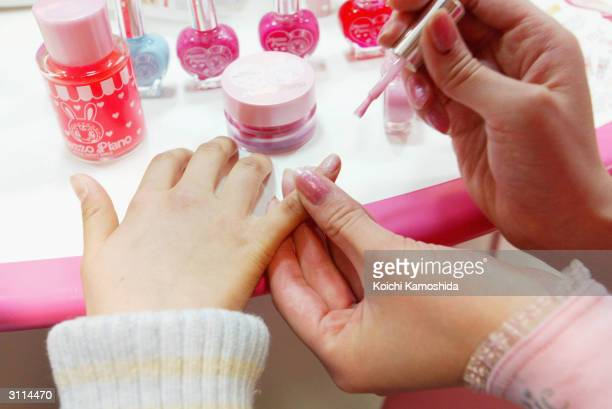 A 10yearold Japanese girl has her nail polish done by a sales assistant at a store of the Japanese toy maker Bandai Co Ltd on March 20 2004 in Tokyo...