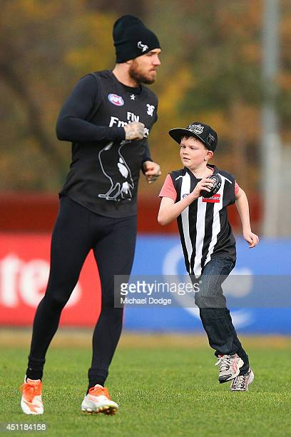 10yearold Peter MacCallum patient Jaxon Cooper runs with Dane Swan during a Collingwood Magpies training session at Westpac Centre on June 25 2014 in...