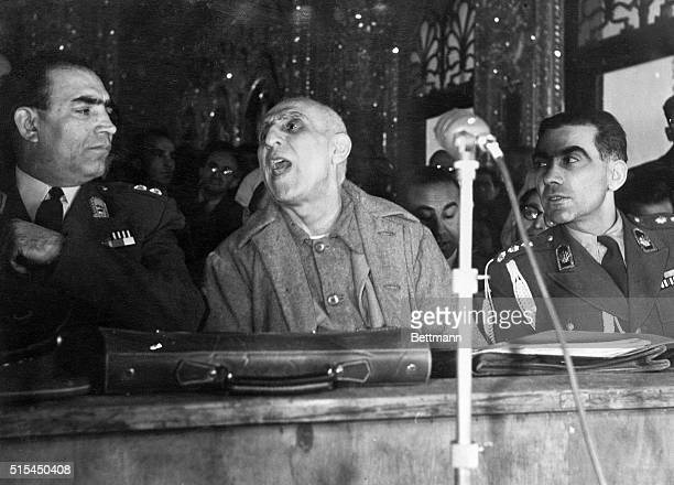 Teheran Iran Flanked by two guards former Iranian Premier Mohammed Mossadegh is shown holding the floor at the opening session of his trial in...