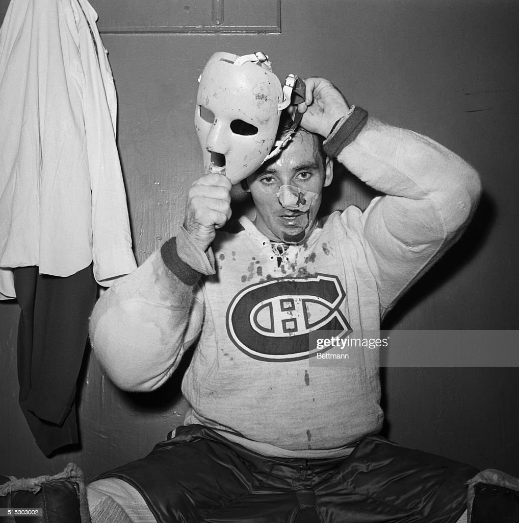 New York, NY- His face and shirt bloodied, Montreal Canadiens goalie <a gi-track='captionPersonalityLinkClicked' href=/galleries/search?phrase=Jacques+Plante&family=editorial&specificpeople=227203 ng-click='$event.stopPropagation()'>Jacques Plante</a> puts on a special plastic mask after being treated for a facial cut received in the opening period of the Rangers-Canadiens hockey game. Plante suffered a severe gash on the left side of his face when he was struck by a shot off the stick of Andy Bathgate of the New York Rangers. After donning the mask, which he had designed himself, Plante returned to the game.