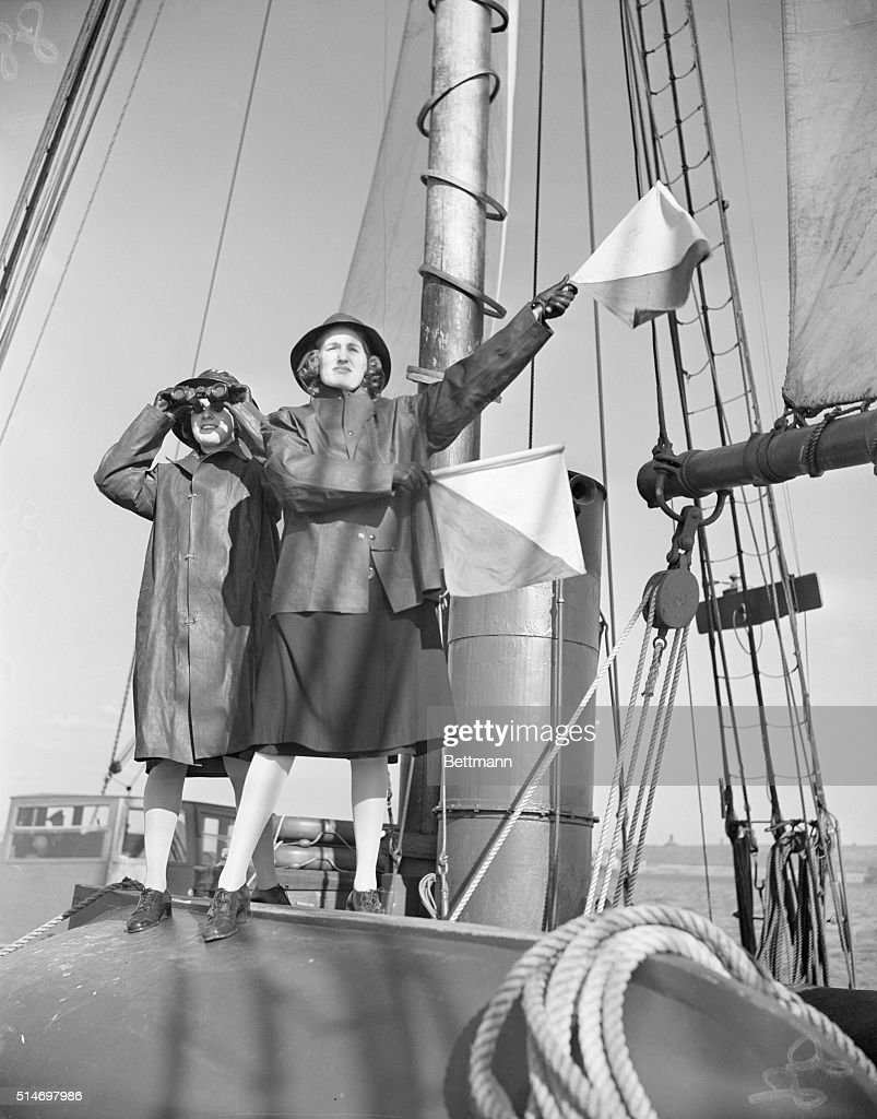 SPAR Thelma I Moore of Cincinnati OH takes a hand at sending a semaphore message while Spar Evangeline R Amaral of East Providence RI uses binoculars...