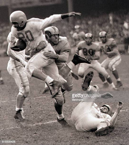 New York NY George Taliaferro of the New York Yanks flying through the air with one wing outsread is brought down to earth by Los Angeles Rams' Paul...