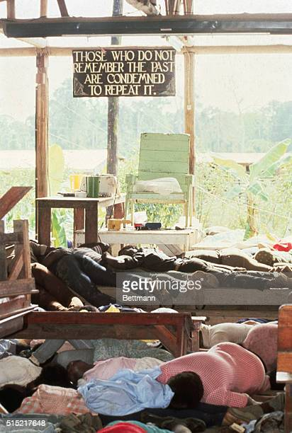 11/23/78Jonestown Guyana Bodies of cultists lie around the 'throne' used by sect leader Jim Jones 11/20 Quotation on sign is from US philosopher...