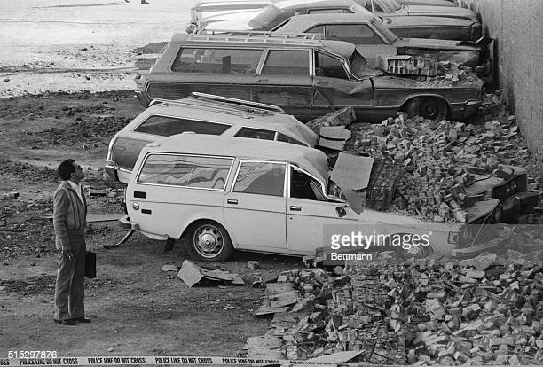 Calexico CA A curious passerby examines parked cars that were crushed by falling bricks from a furniture store wall that collapsed in the 63...