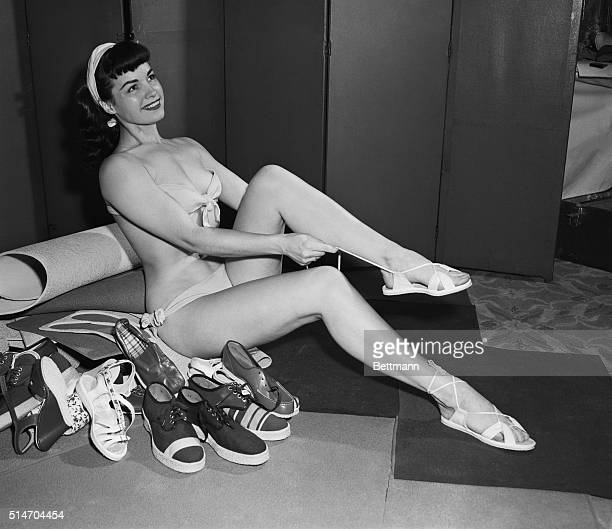 New York NY Lovely Bettie Page wearing a highlydistracting swimsuit tries on a pair of sandals at a show for new shoes in New York One of the most...