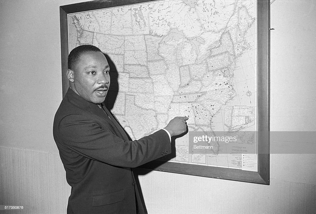 Dr. Martin Luther King points to Selma, Alabama on a map at a Southern Christian Leadership Conference office, as he calls for a three-pronged attack on racial barriers. Negro leaders indicate that January 18 will bring the biggest organized test to date of the new Civil Rights law. Volunteers are scheduled to march on the voter registration office, while others, too young to vote, will test the public accomodations section of the act. Still others will seek employment.
