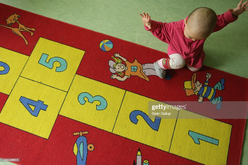 11-month-old Lucy crawls in the playroom of the 'Jule' facility for single parents as her mother nancy Kett, 19, (not pictured) looks on in Marzahn-Hellersdorf district on October 5, 2012 in Berlin, Germany. The Jule project helps single parents by helping them to find jobs, job training and housing, advice on child development and day care in Marzahn-Hellersdorf, a district in east Berlin with high levels of unemployment and social problems. Currently 14 single mothers and one single father are participaring at Jule, which opened its doors in the spring of 2012.