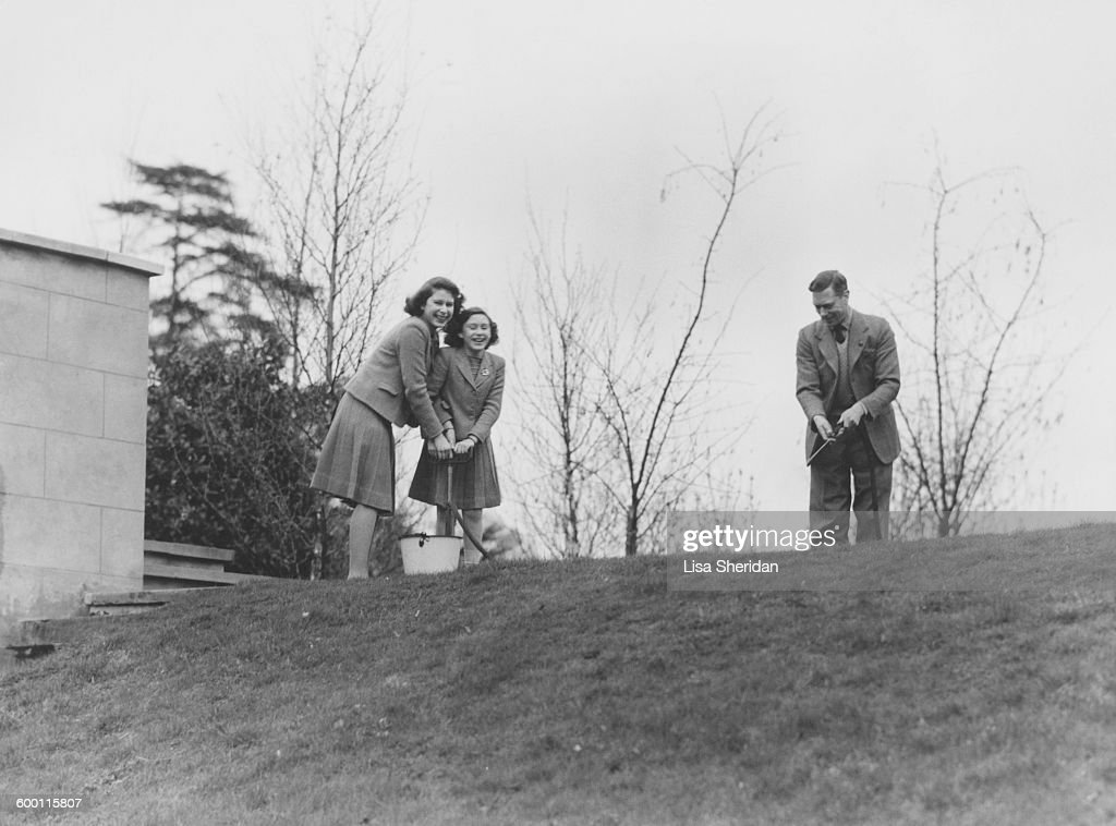 Princess Margaret Rose (1930 - 2002) and Princess Elizabeth pumping water from a bucket as their father, King George VI (1895 - 1952) wields the hose, in the grounds of the Royal Lodge, Windsor.