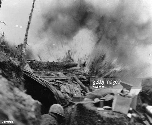 US Marines duck for cover in a bunker in Korea as an 82mm shell explodes during the Korean War