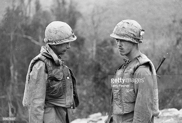 Two US soldiers in Vietnam in flakjackets and cloth covered steel helmets