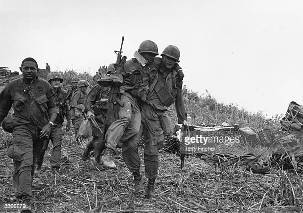 US soldiers one wounded and being carried by a colleague walking down Hill Timothy during the conflict in Vietnam