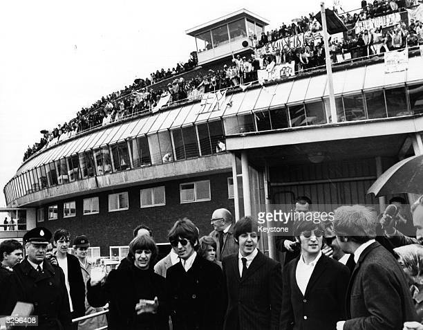 Crowds of screaming fans turned out on the roof of the Queen's Building at London Airport to bid British pop group The Beatles farewell as they left...