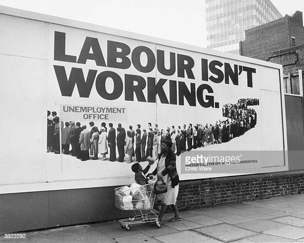A woman with her shopping and little boy in a shopping trolley walk past a poster supporting the Conservative Party during the run up to the General...