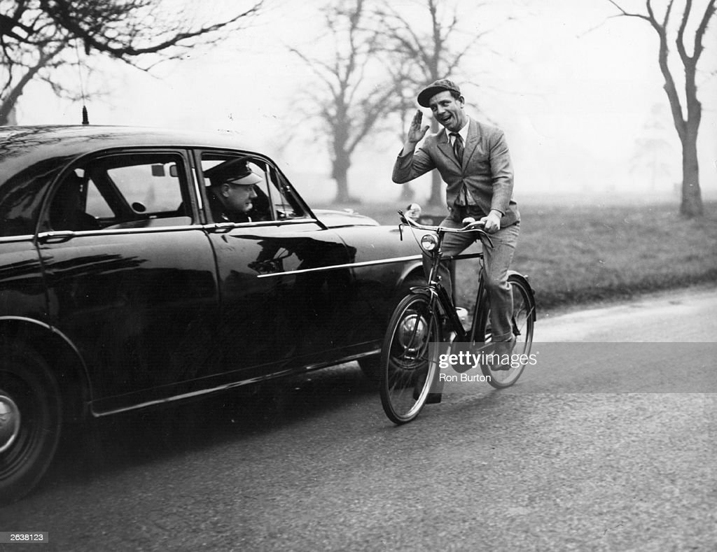 Norman Wisdom, slapstick comedian of stage, screen and television waves to a police man in his car.