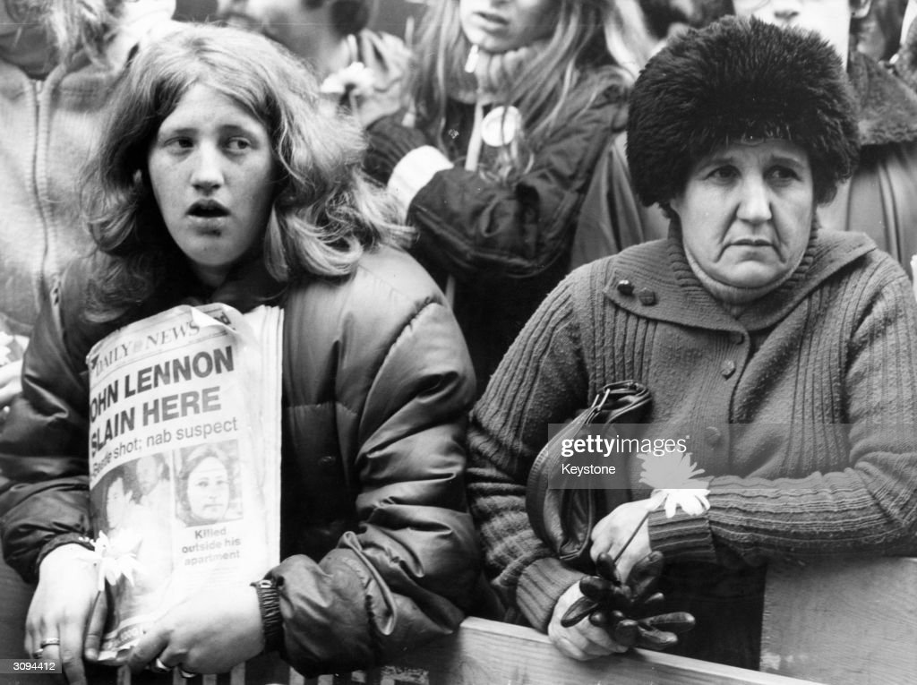 Fans of John Lennon holding a vigil outside his apartment after he was shot dead in New York