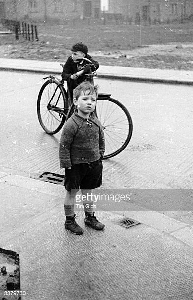 A confusedlooking boy playing on a street in Durham Original Publication Picture Post 86 Unemployed pub 1939