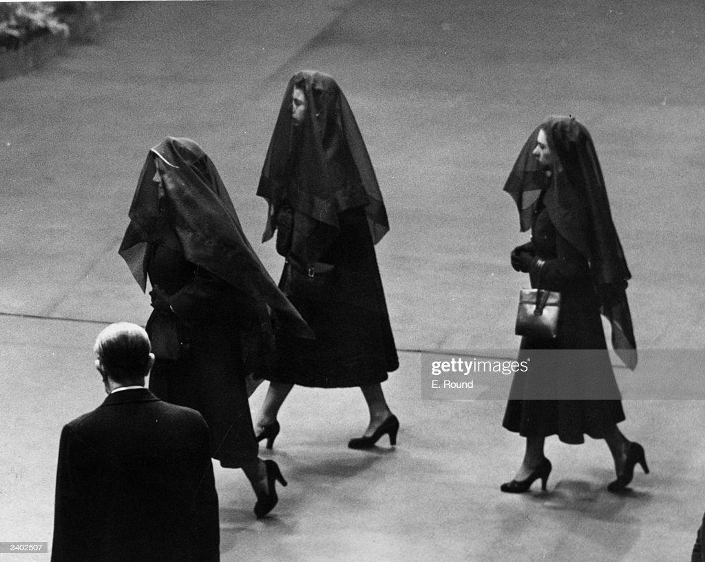 Left to right Queen Elizabeth the Queen Mother Queen Elizabeth II and Princess Margaret Rose wearing veils during their journey between Sandringham...