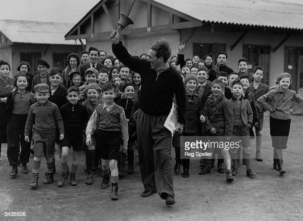 A camp leader ringing the dinner bell at a camp for young Jewish 'Kindertransport' refugees from Germany and Austria at Dovercourt Bay near Harwich