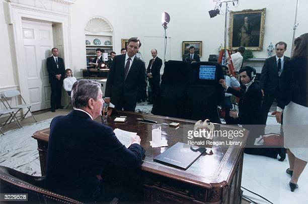 Rear view of US President Ronald Reagan at his desk in the Oval Office looking at a teleprompter as he delivers his televised farewell address to the...