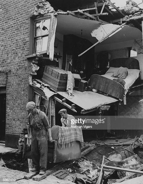 Workmen carry out salvaged furniture from a house in Bow East London after it was flooded by a burst water main