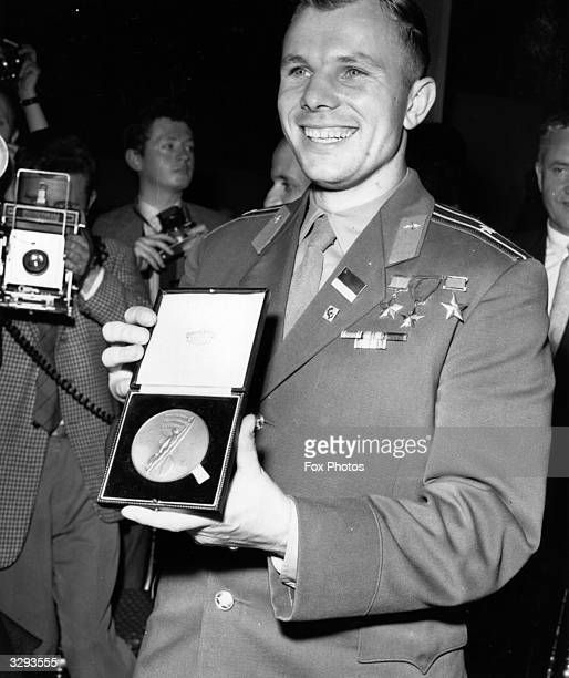 Major Yuri Gagarin showing off a medal awarded to him by the British Interplanetary Society at a London press conference The Russian cosmonaut became...