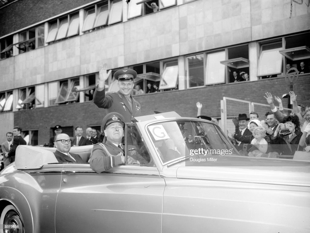 Soviet astronaut Yuri Gagarin, who became the world's first man in space, acknowledges the crowd on his arrival in Britain, as he leaves London Airport in a Rolls Royce.