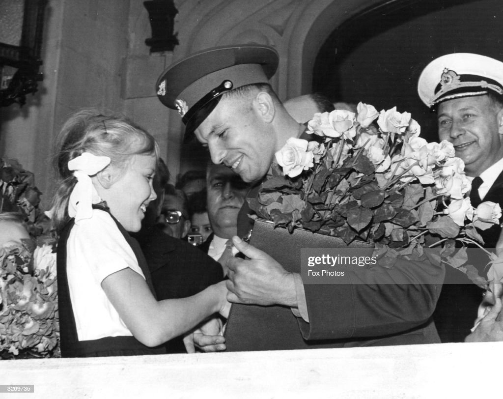 The world's first cosmonaut Major Yuri Gagarin of the Soviet Union receives a bouquet of flowers from a little girl on arrival at the Soviet Embassy in London.