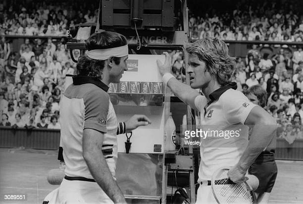 On the left Argentinian tennis player Guillermo Vilas stands at the umpire's chair chatting to actor Dean Paul Martin on Wimbledon's centre court The...