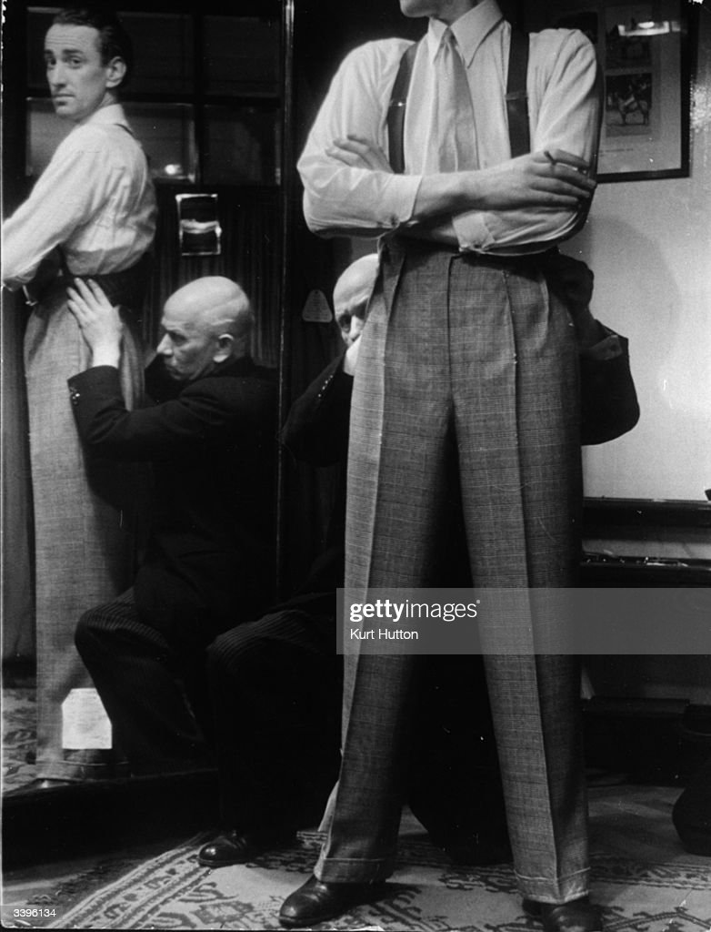 The first part of the suit to be fitted is the trousers. A trouser expert at Savile row makes sure the garment drapes straight down the back and front of the leg. Original Publication: Picture Post - 100 - Making A Savile Row Suit - pub. 1939