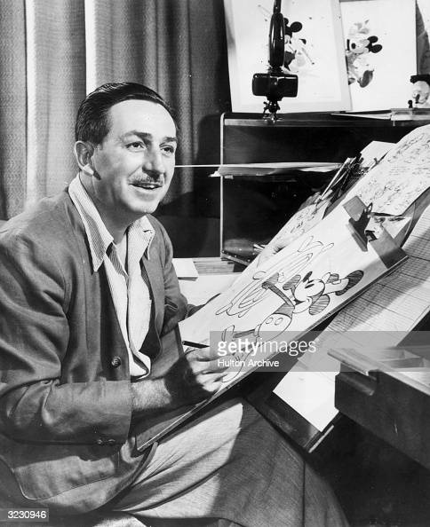 American animator and motion picture studio founder Walt Disney sits at his drawing board in his studio drawing a sketch of his character Mickey...