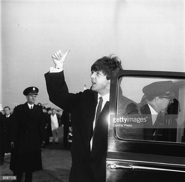 Paul McCartney of The Beatles pop group gives the thumbs up to fans waiting on the roof of the Queen's building at London Airport on the group's...