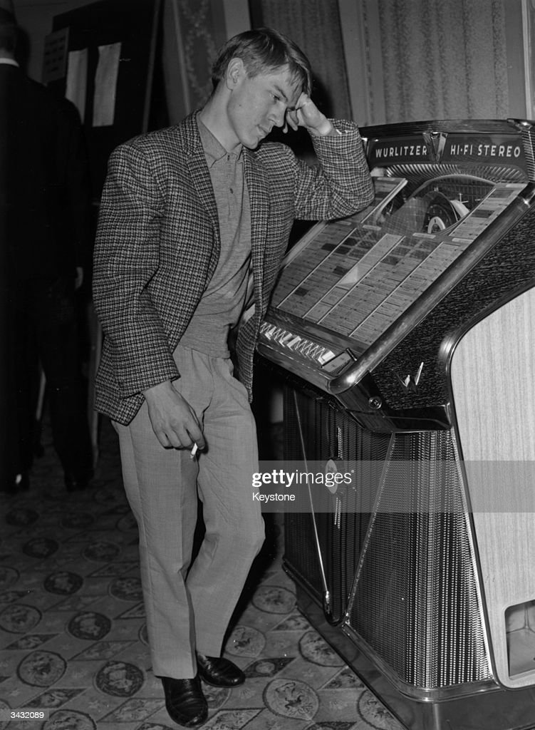 Singer and television actor Adam Faith (1940 - 2003) listens to a juke box at a Variety Club of Great Britain 'Golden Disc' luncheon held at the Dorchester Hotel, London.