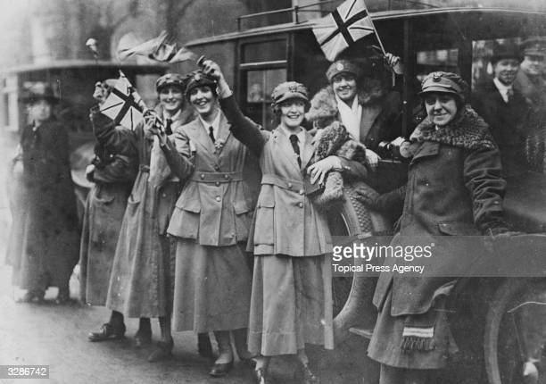 Women of the Women's Royal Australian Naval Service waving flags on Armitice Day in London