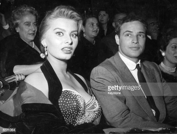 Italian actress Sophia Loren and US actor Marlon Brando at a cinema in Rome where Brando received the Francesco Pasinetti Prize for his performance...