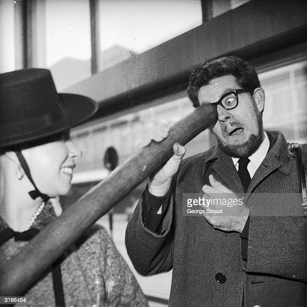 Australian entertainer Rolf Harris looking down the end of his didgeridoo at London Airport his wife Alwyn Harris is with him