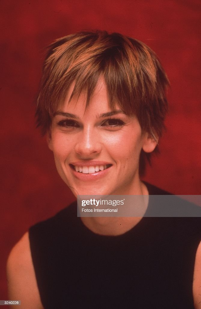 Headshot of American actor Hilary Swank wearing a black tank top and smiling during a press conference, Beverly Hills, California. That month was the premiere of director Kimberly Peirce's film, 'Boy's Don't Cry,' in which Swank gave an Oscar-winning performance.