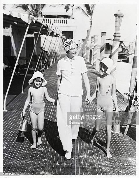 Miami Beach FL Mrs Walter Winchell wife of the New York columnist shown with her two daughters Gloria and Walda on the promenade of the Roney Plaza...