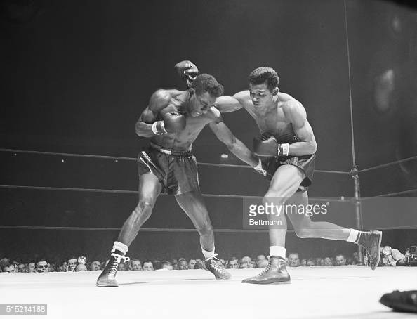 New York NY Tommy Bell of Youngstown Ohio ducks just in time as Ray 'Sugar' Robinson of New York rolls a right over his shoulder in a 15round...
