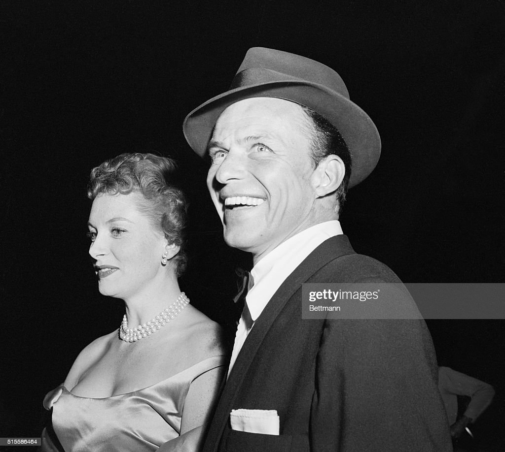 A dapper, radiant Frank Sinatra, one of the stars of the film, arrives at this 'Guys and Dolls' movie premiere with Deborah Kerr. Cleo Moore's camera captured the actor-singer's wide, wide smile. Photo dated 12/2/55.