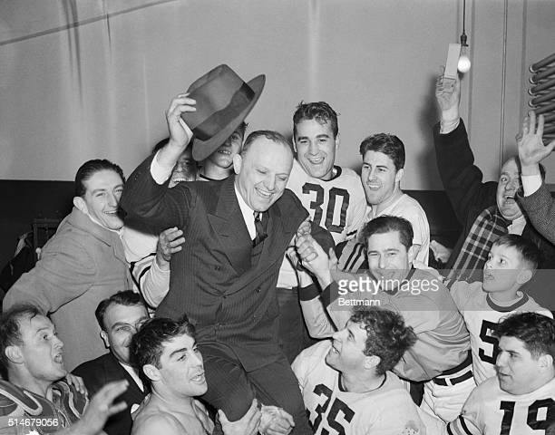 Jubilant Chicago Bears hold aloft their ownercoach George Halas after they snowed under the Washington Redskins 730 at Washington to win the National...