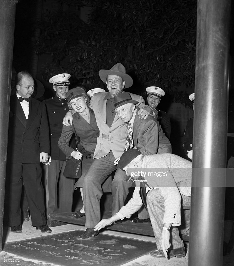 Movie actor John Wayne (center) is aided by Marine Pvt. Inga Boberg (left) and Sid Grauman (second from right) as he puts his foot into the cement in the court of the famed Grauman's Chinese Theater. Mixer Jean Klossner makes sure that the impression is a good one. Wayne is the 112th star to be so honored and was chosen because of his performance in 'Sands of Iwa Jima,' a Marine Corps. epic. BPA2 #1877