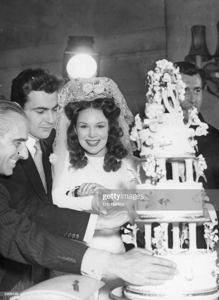 Jean Kent, star of several Gainsborough films, cutting the cake at the reception following her wedding to Hungarian actor Yusef Ramart, whom she met while filming 'Caravan'.