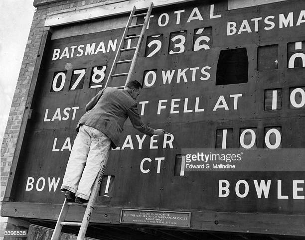A painter appling a final coat of paint to Sussex County Cricket score board