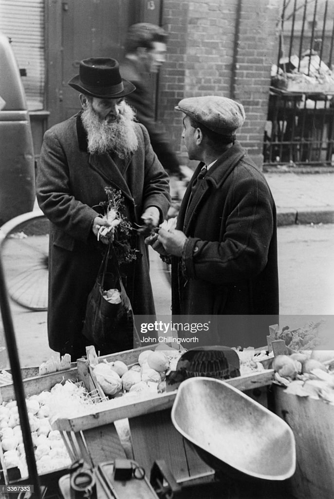 A bearded Jewish man buying vegetables at a stall in Whitechapel east London Original Publication Picture Post 5829 Passover Story Whitechapel's Jews...