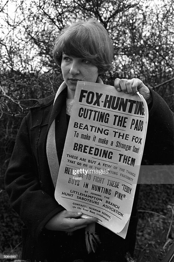 A member of the Littlehampton Hunt Saboteurs holds up a poster detailing some of the barbaric practices involved in fox hunting.