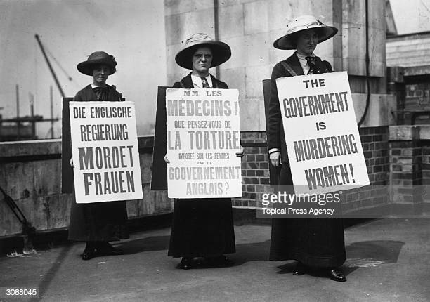 Three suffragettes wearing sandwich boards in English French and German protest against the British government's policies regarding women The...