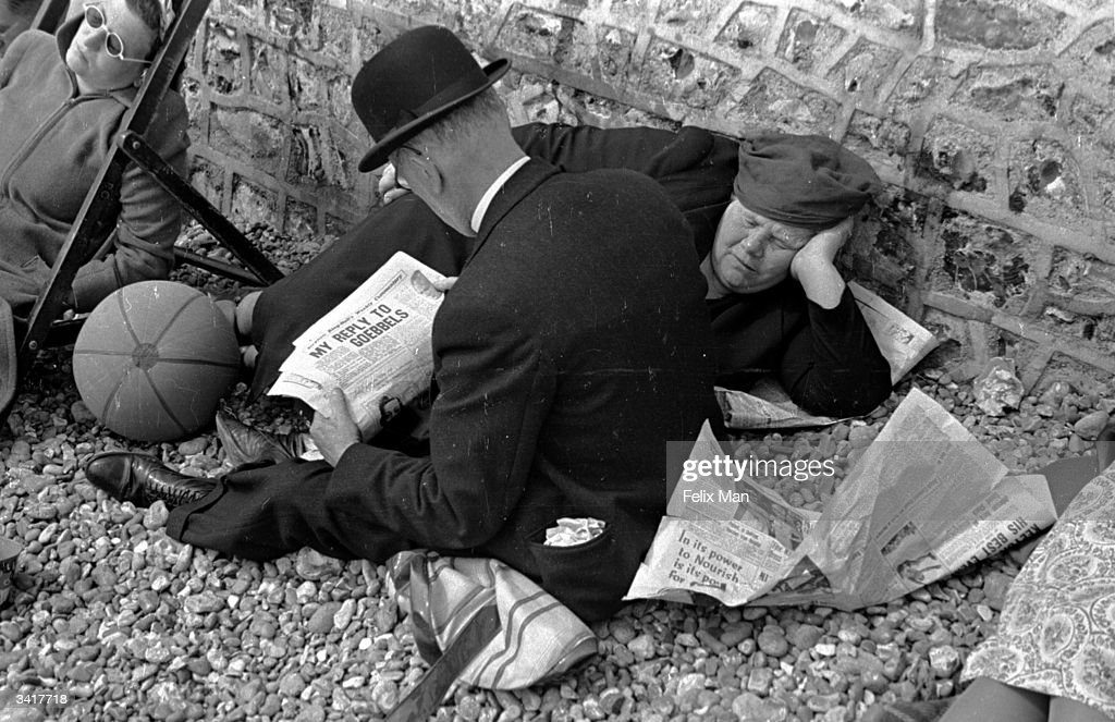 On Brighton beach a man reads a newspaper with news of the impending war while his wife sleeps. Original Publication: Picture Post - 171 - Brighton - pub. 1939
