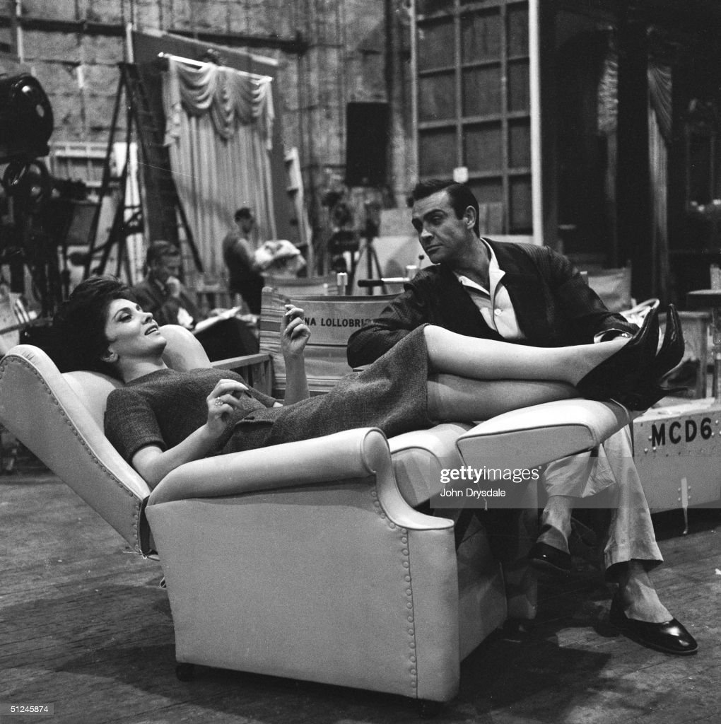 12th August 1963, Gina Lollobrigida and Sean Connery resting between takes of their latest film 'Woman of Straw', directed by Basil Dearden. Gina lies back in a special adjustable armchair.