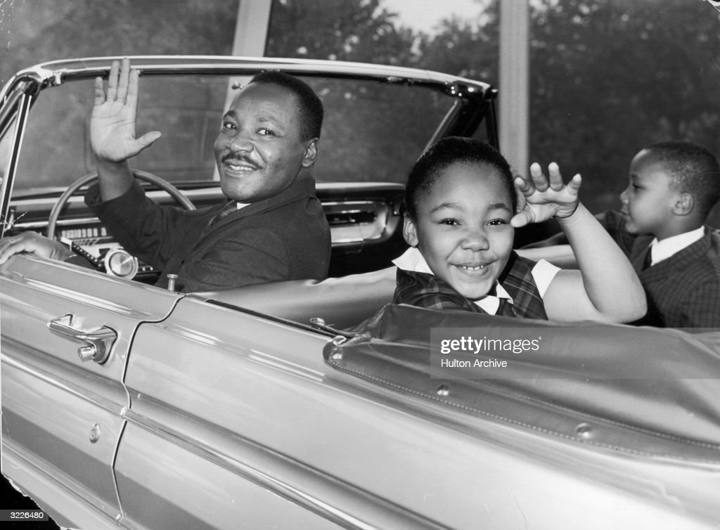 American civil rights leader Martin Luther King Jr. (1929 - 1968) waves with his children, Yolanda and Martin Luther III, from the 'Magic Skyway' ride at the Worlds Fair, New York City. The ride was a replica of a Ford convertible.
